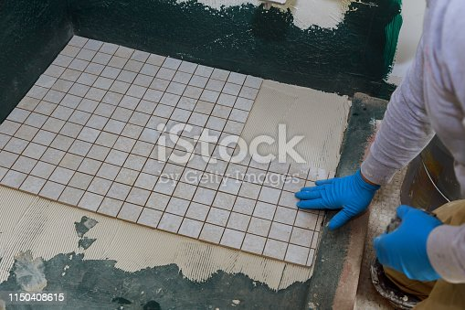 1138442636 istock photo Troweling mortar a concrete floor in preparation for laying floor tile. 1150408615