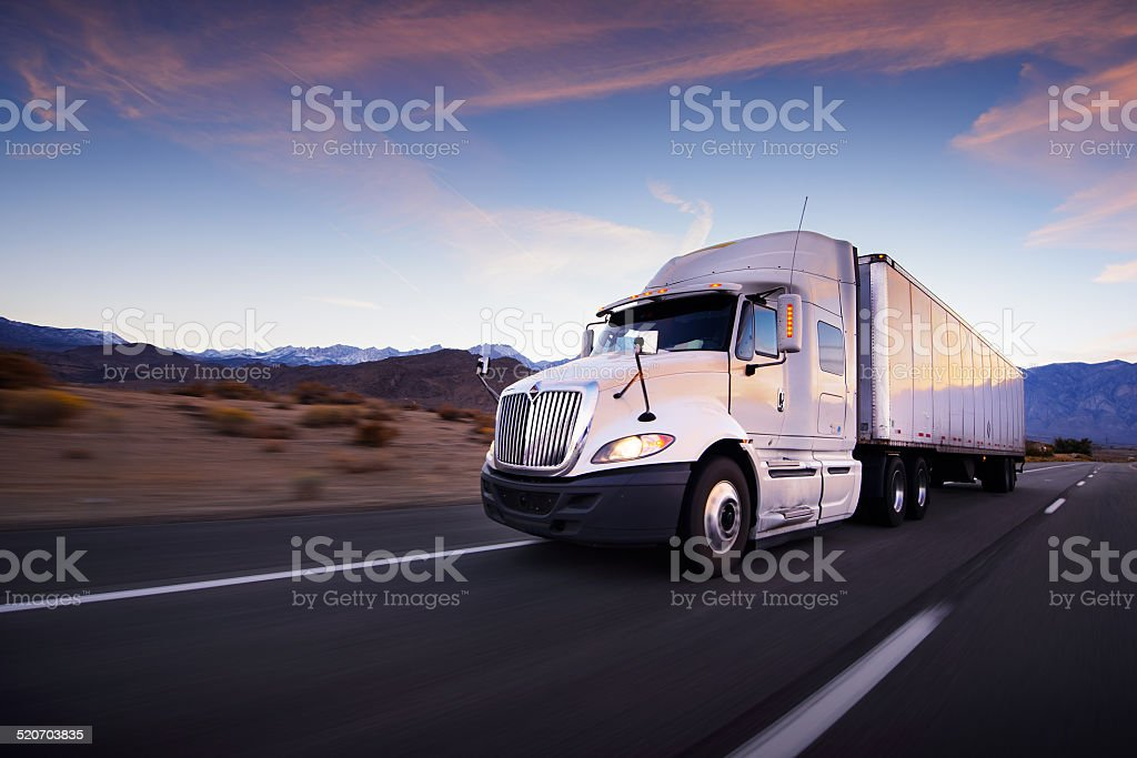Truck and highway at sunset - transportation background stock photo