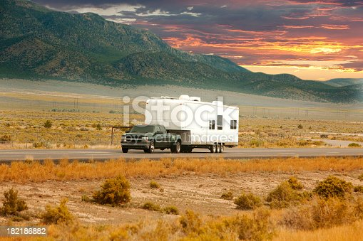 An RV heads down a scenic road at sunset.