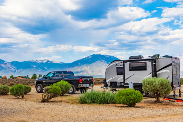 Truck and RV trailer camped in southwest, with mountain range behind. stock photo