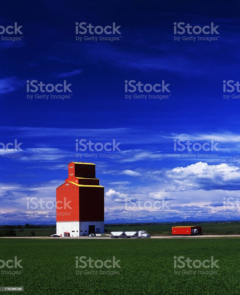 Truck and trailer drives away from grain elevator royalty-free stock photo