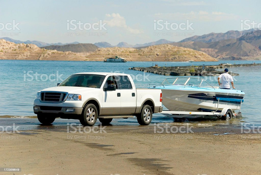 A truck backing a boat off of a trailer and into the water stock photo