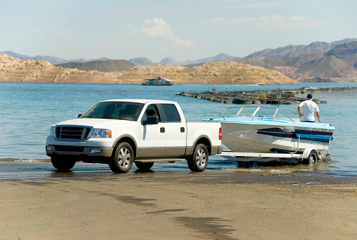 A Truck Backing A Boat Off Of A Trailer And Into The Water ...
