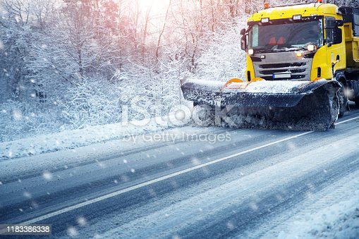 Truck cleaning on winter road covered with snow. Vehicle on snowy alley in the morning at snowfall