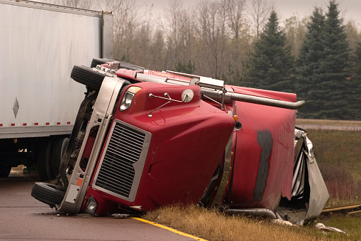 Transport truck crashed with jack knifed trailer lays on side of freeway.There's more truck accident scenes in my portfolio.