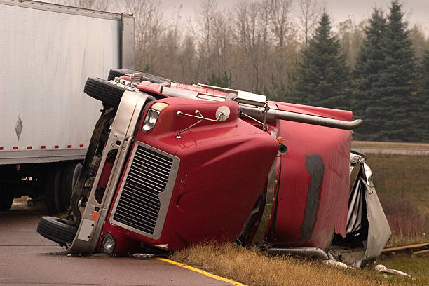 Truck crash with turned over semi Transport truck crashed with jack knifed trailer lays on side of freeway.There's more truck accident scenes in my portfolio. misfortune stock pictures, royalty-free photos & images
