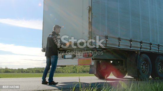 Truck Driver Closes Doors of His Parked  Truck Cargo Trailer. Professional Driver Wears Heavy Duty Gloves.