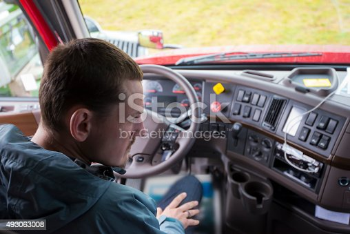 The truck driver sitting in the cab of modern comfort and ergonomic semi truck behind the wheel and interior dashboard with numerous control buttons and switches. The driver of semi truck assessment the situation, looking in the right rearview mirror.