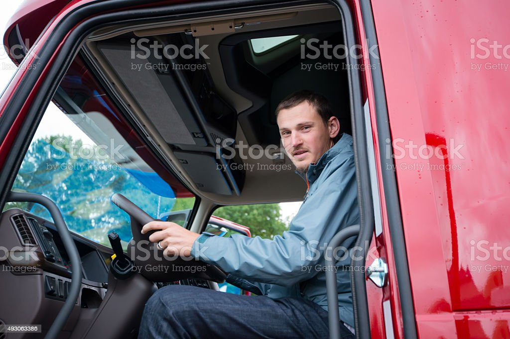 Truck driver in semi truck cab with modern dashboard stock photo