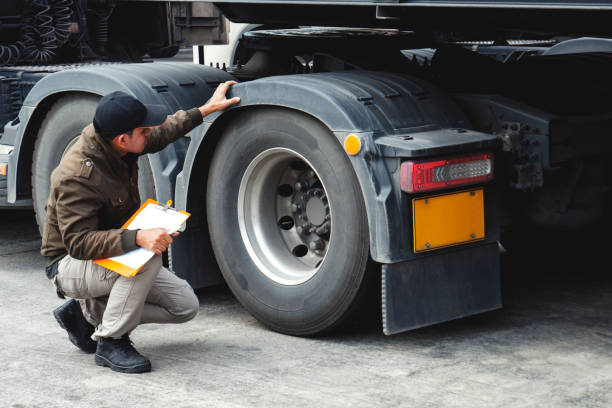 truck driver inspecting safety check a truck tires - transport truck tyres foto e immagini stock