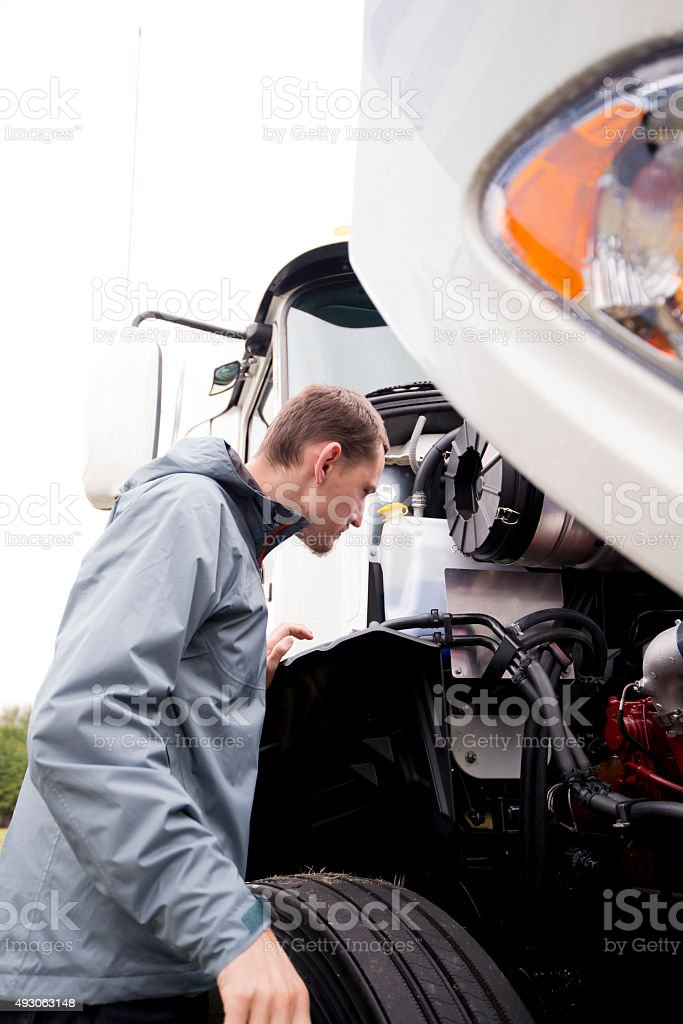 Truck driver inspecting white big rig semi truck engine stock photo