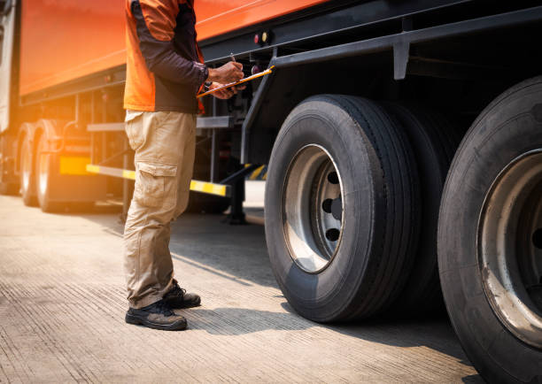 truck driver is inspecting safety tires truck. - truck tire foto e immagini stock