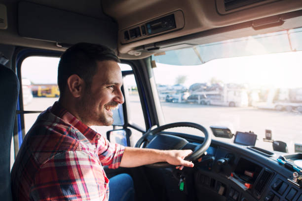 Truck driver job. Middle aged trucker driving truck. Professional middle aged truck driver in casual clothes driving truck vehicle going for a long transportation route. driver occupation stock pictures, royalty-free photos & images