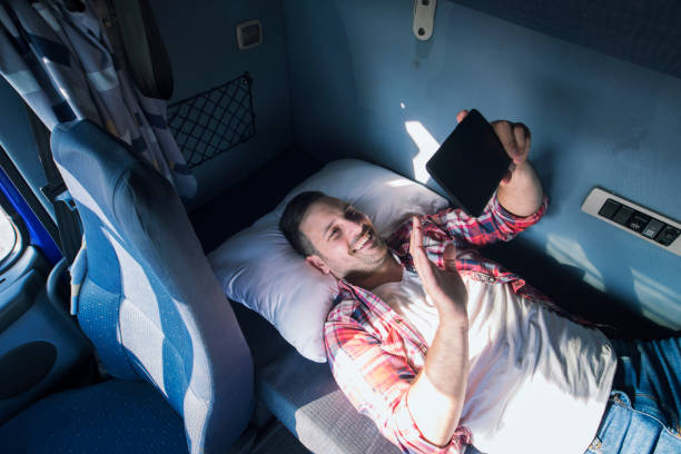 Truck driver missing his family. Truck driver separated from his family lying on the bad of his truck cabin and waving to his wife and children via tablet computer. Trucker lifestyle missing family. passenger cabin stock pictures, royalty-free photos & images