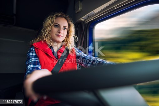 Female truck driver steering and driving truck vehicle.