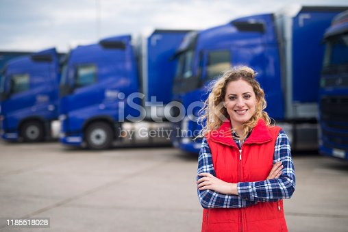 Portrait of female truck driver standing by trucks at truck stop.