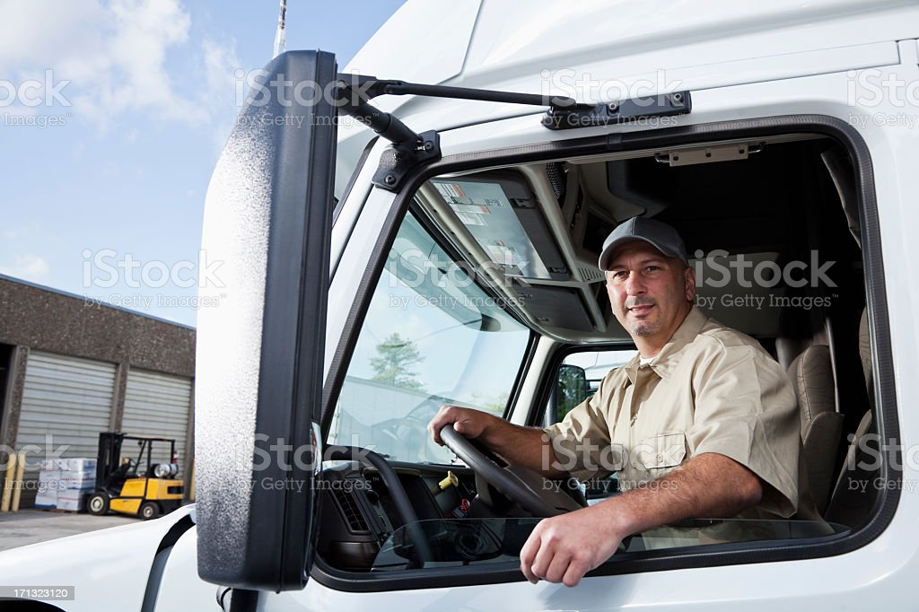 Truck driver sitting in cab of semi-truck stock photo