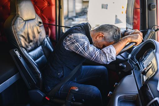 Exhausted truck driver falling asleep on steering wheel.