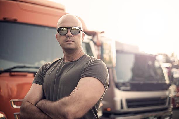conductor de camión pie en frente de la flota de camión - hombres grandes musculosos fotografías e imágenes de stock