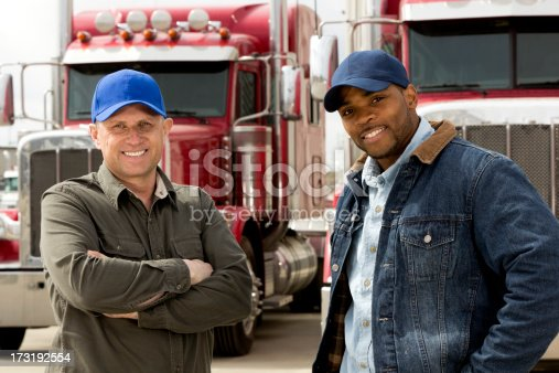 A royalty free image from the trucking industry of two smiling truck drivers standing in front of their trucks.