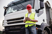 Truck driver or construction worker us ing a mobile app next to a truck. About 45 years old, Caucasian mature adult man.