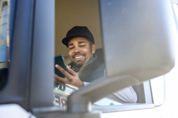 Truck driver using a mobile app stock photo