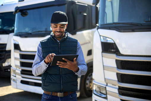 Truck driver using a tablet. About 35 years old, African male.