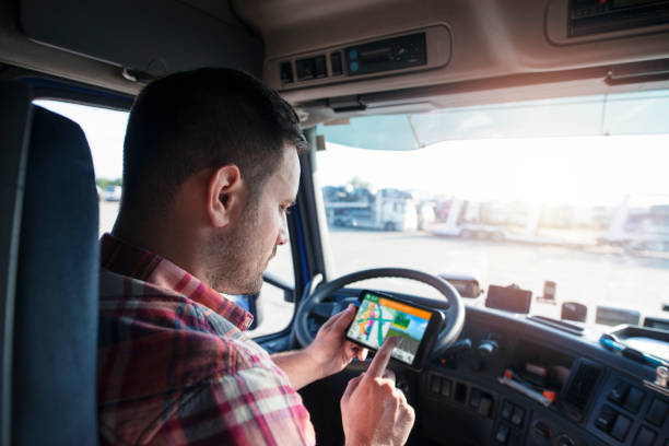 Truck driver using GPS to deliver goods. Transportation services with global positioning system. Professional middle aged trucker using truck GPS navigation to transport and deliver goods to the destination. Transportation services. global positioning system stock pictures, royalty-free photos & images