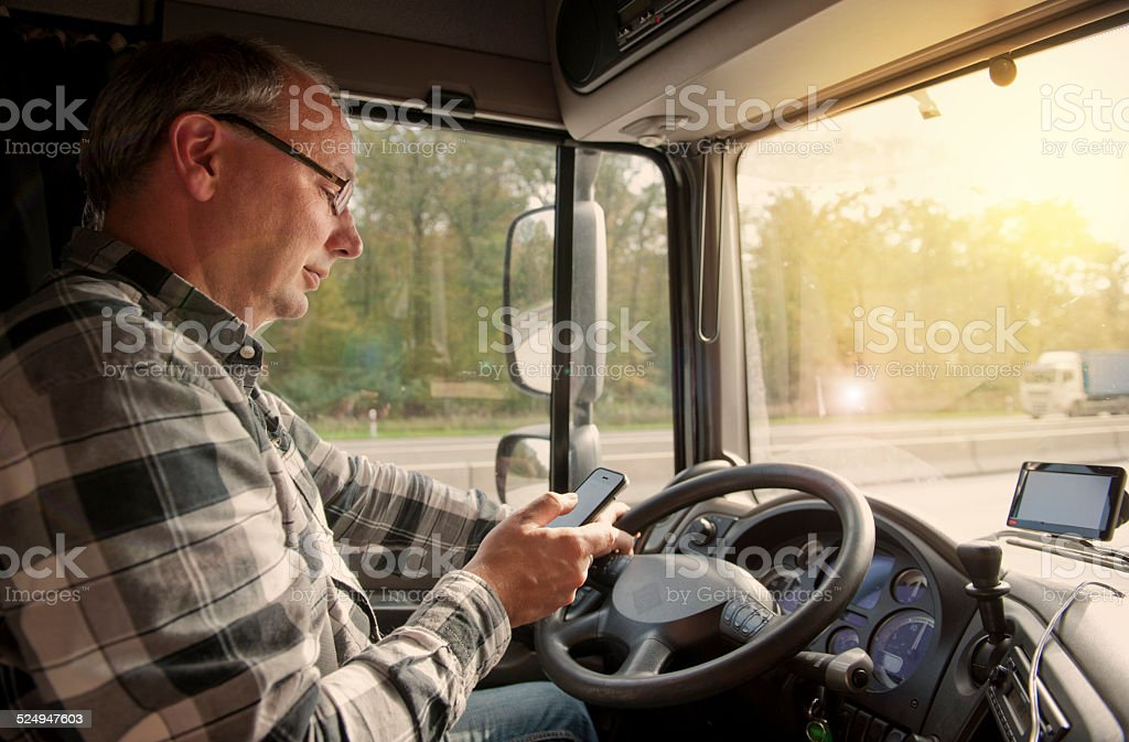 Truck driver using mobile phone stock photo