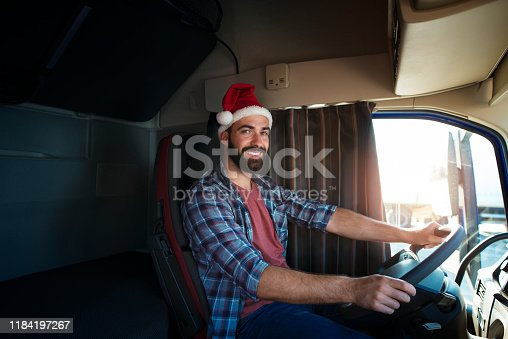 Truck driver wearing Santa Clause hat and driving his truck on Christmas. People working on holidays. Trucker lifestyle. Merry Christmas.