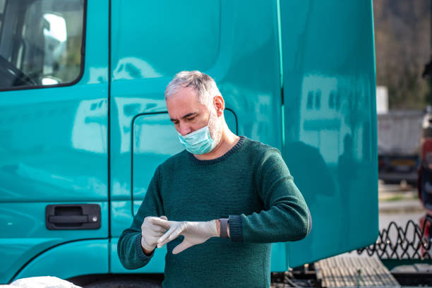 Truck Driver with face mask and surgical gloves during COVID-19 crisis Truck Driver with face mask and surgical gloves during COVID-19 crisis driver occupation stock pictures, royalty-free photos & images