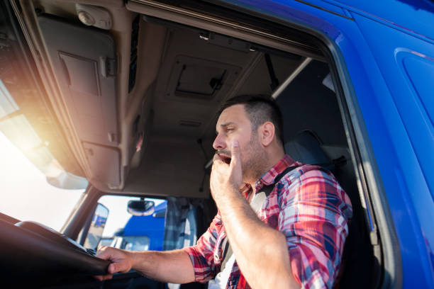 truck driver yawning while driving. tired people overworking. - stanco foto e immagini stock