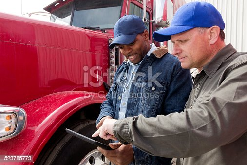 A royalty free image from the trucking industry of two truck drivers having a conversation and using a tablet computer in front of a red semi truck.