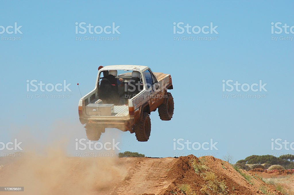 Truck driving off a ramp while off-road racing stock photo