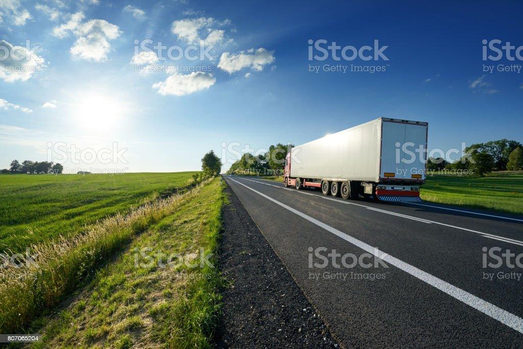 LKW-fahren auf asphaltierten Straße in ländlichen Landschaft bei Sonnenuntergang – Foto