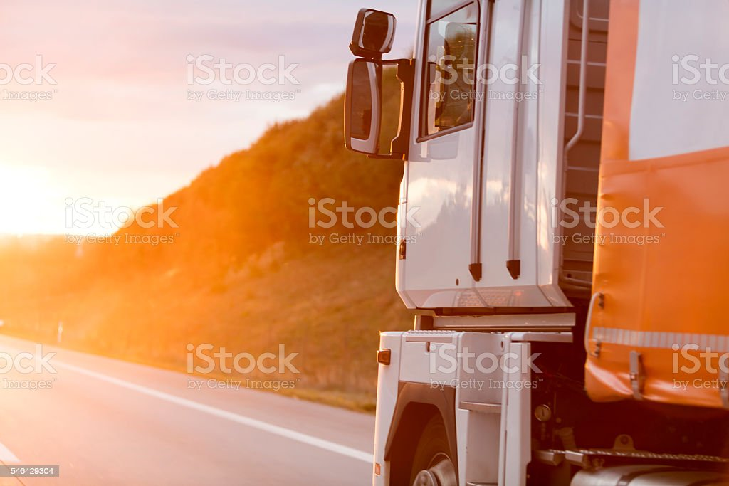 Truck driving on highway at sunset stock photo