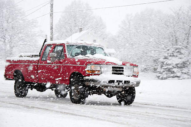 Truck Driving on snowy road during storm stock photo