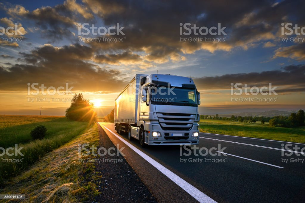 Truck driving on the asphalt road in rural landscape at sunset with dark clouds stock photo