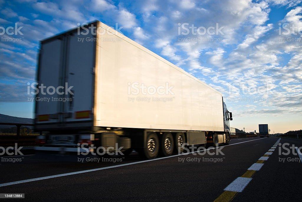 LKW-fahren auf der Autobahn vor blauem Himmel bei Sonnenuntergang – Foto