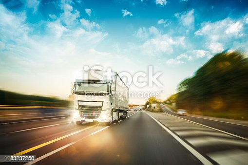 Truck driving fast during delivery on the motorway asphalt road