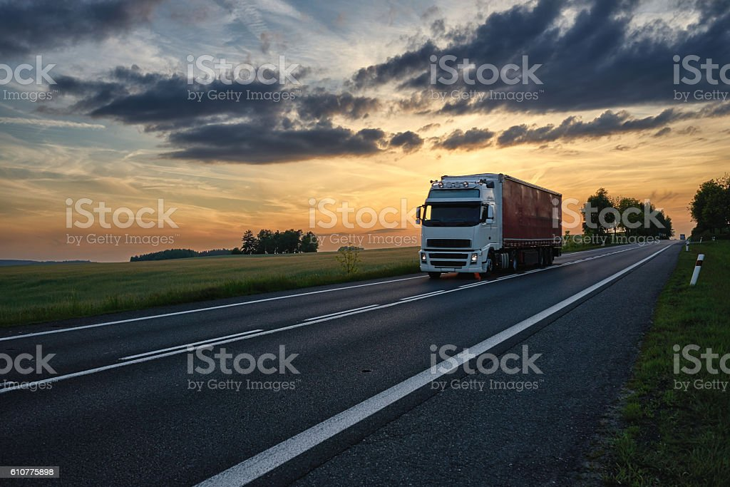 Truck driving on the road at sunset. stock photo