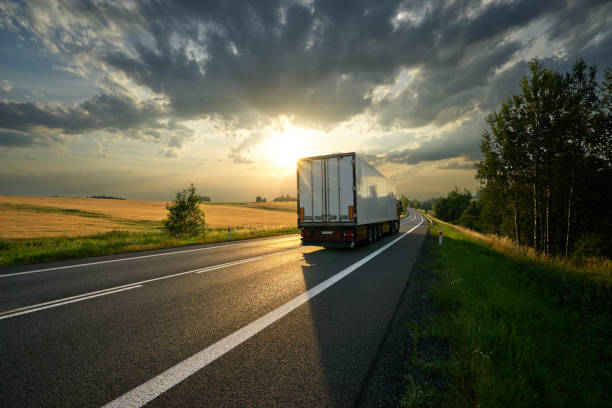 Truck driving on the road in rural landscape at sunset - foto stock