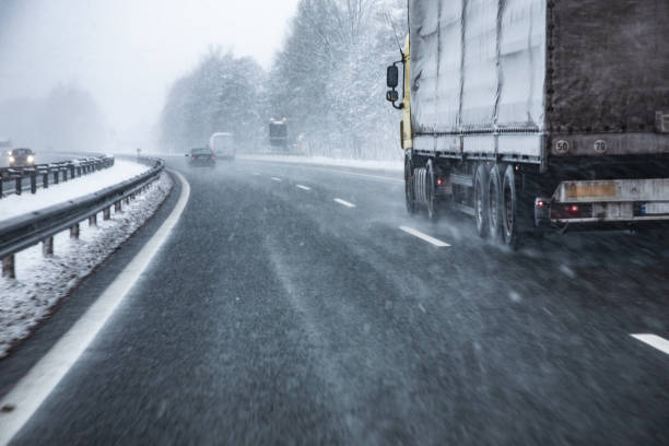 truck driving on wet and slippery highway in winter - storm stock photos and pictures