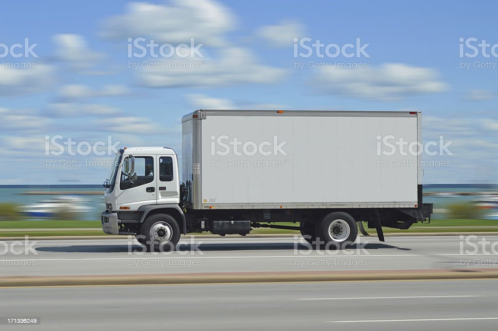 A truck flying by on the highway near the water stock photo