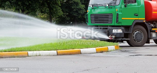 A truck for watering the lawn pours water on the lawn with water jets. City lawn care services.