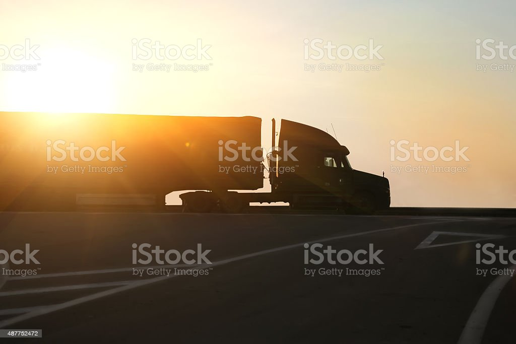 truck goes on highway on sunset stock photo