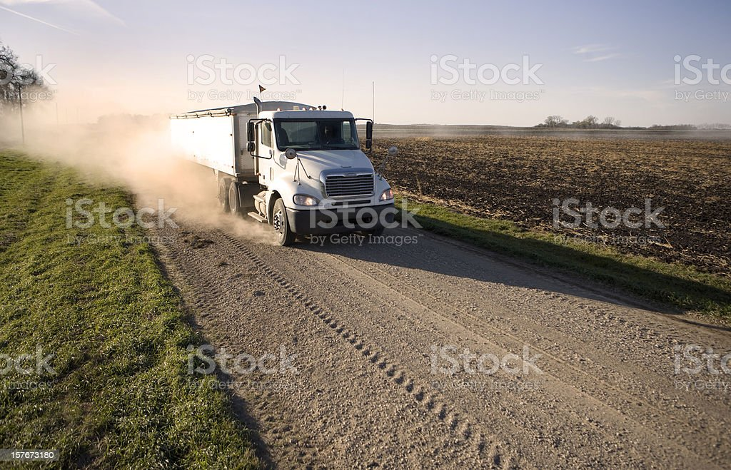 Truck hauling grain on a dusty rural midwest road. stock photo