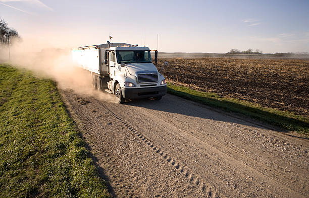 Truck hauling grain on a dusty rural midwest road.
