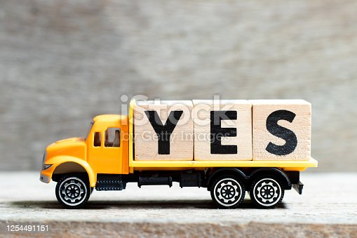 Truck hold letter block in word yes on wood background