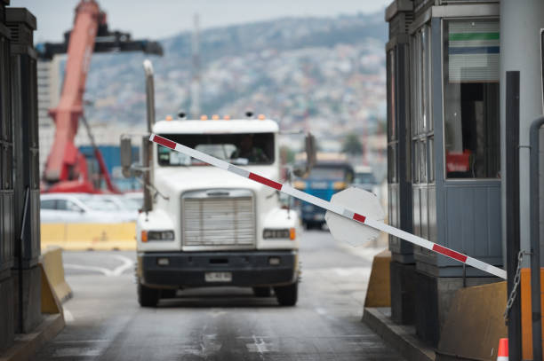 Truck in industrial port area being let through customs - foto stock